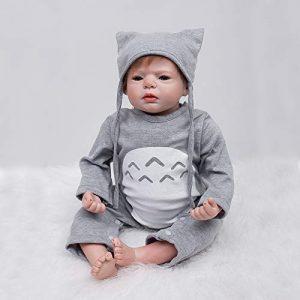 Ce poupon reborn est un petit garçon vêtu de vêtements gris.