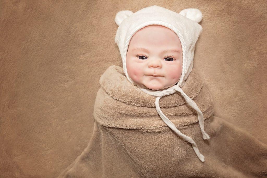 Questo bambino rinato indossa un cappello da orsacchiotto.